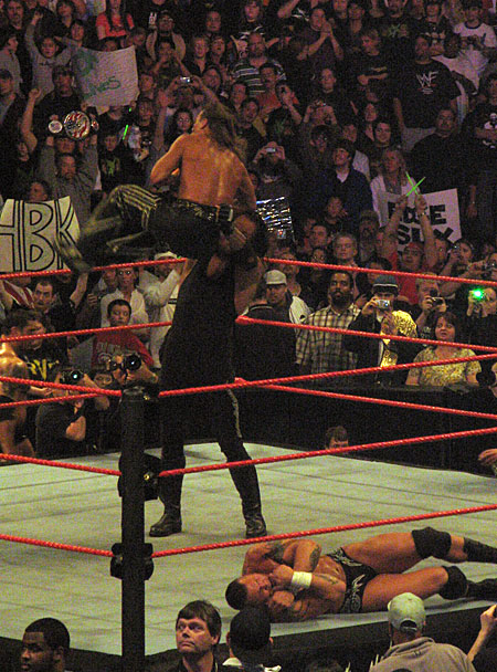 The 7-foot tall Undertaker choke-slams Shaun Michaels as Randy Orton rolls out of the ring